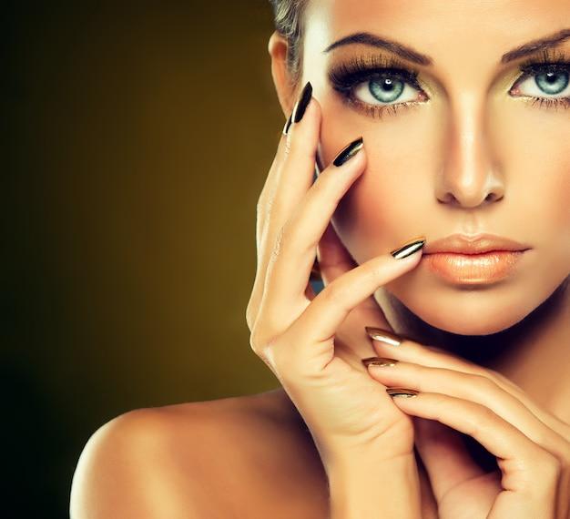 Close-upportret van een jonge vrouw in een chique avondmake-up, grote wimpers en vergulde nagellak