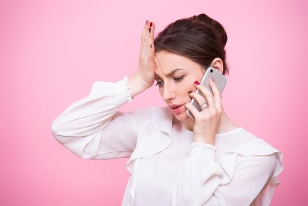 Close-upportret van een jonge vrouw in een pak met een mobiele telefoon in haar handen