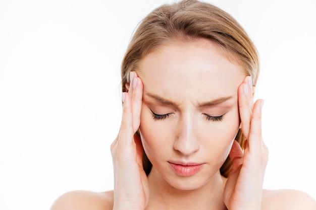 Close-upportret van een jonge vrouw met hoofdpijn die op een witte achtergrond wordt geïsoleerd