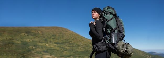 Close-upportret van een jonge vrouwentoerist met een grote rugzak. tegen de achtergrond van de bergen