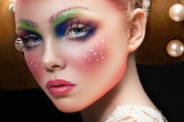 Close-upportret van een kaukasisch vrouwelijk model met creatieve fee clolorful make-up