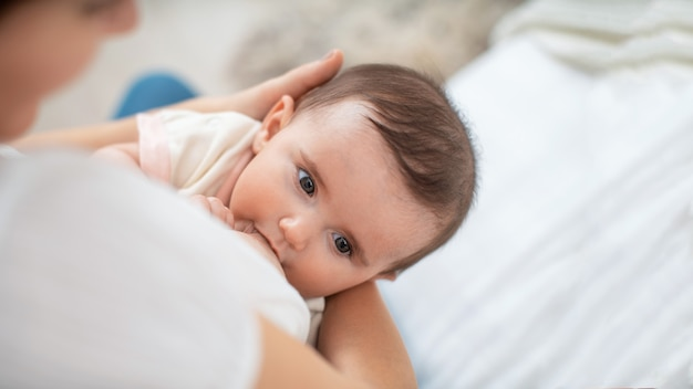 Close-upportret van een kind zuigende melk van de borst van zijn moeder.