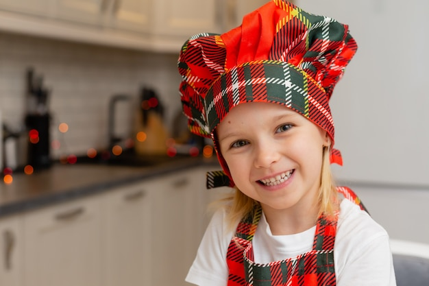 Close-upportret van een klein gelukkig glimlachend blondemeisje in een chef-kokkostuum in de keuken