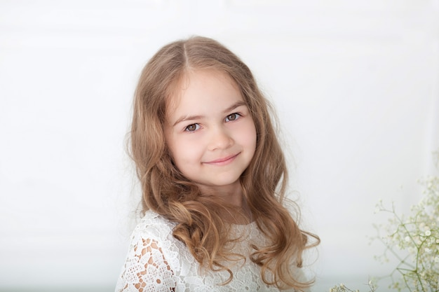 Close-upportret van een klein glimlachend meisje. charmant klein meisje met blond haar in een witte jurk. 8 maart, internationale vrouwendag, moederdag. portret van een gelukkig glimlachend kindmeisje. childhood