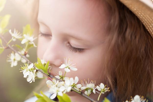 Close-upportret van een klein kaukasisch meisje van 5 jaar oud dat geniet van de geur van kersenbloesems in een park dat onder een bloeiende kersenboom staat