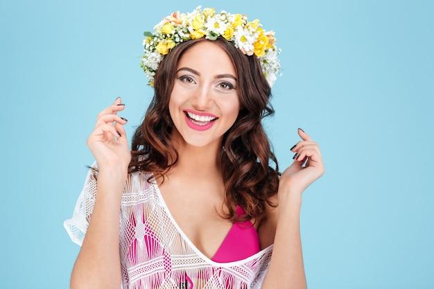 Close-upportret van een lachende mooie vrouw die bloemdiadeem draagt dat op de blauwe achtergrond wordt geïsoleerd