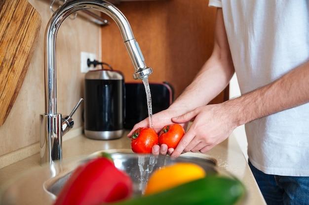 Close-upportret van een mannelijke handen die groenten wassen