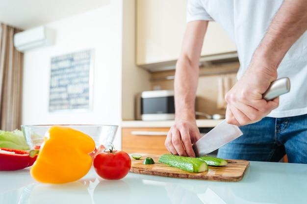 Close-upportret van een mannelijke handen die komkommer snijden bij de keuken