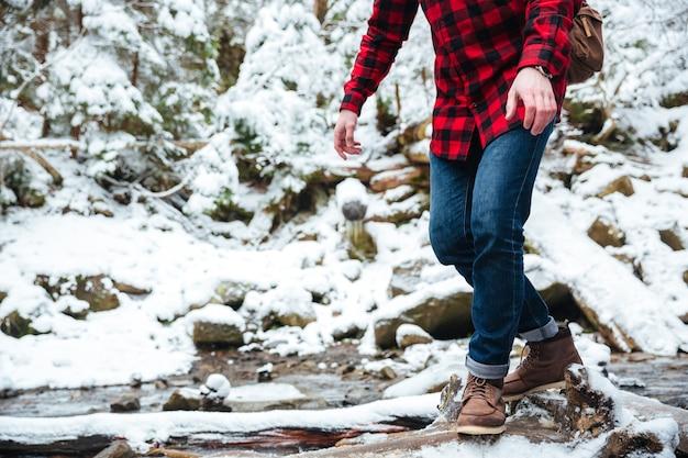 Close-upportret van een mannelijke wandelaar die op bergrivier met sneeuw loopt