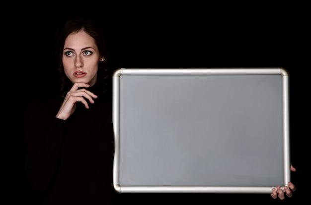 Close-upportret van een meisje met lichte huidskleur met donker haar. portret van een aantrekkelijk modern meisje met een speelse uitstraling, op een zwarte achtergrond. kopieer ruimte