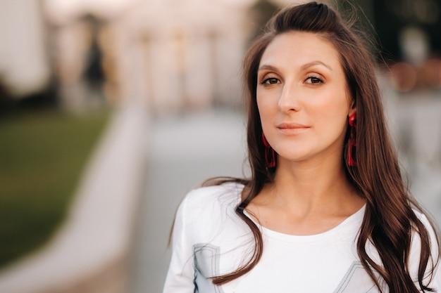 Close-upportret van een meisje met rode oorringen in witte kleren in de stad
