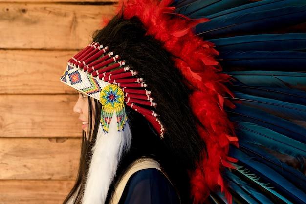 Close-upportret van een mooi meisje dat native american indian chief hoofdtooi draagt