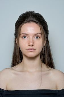 Close-upportret van een mooie jonge donkerbruine vrouw met lang haar zonder make-up