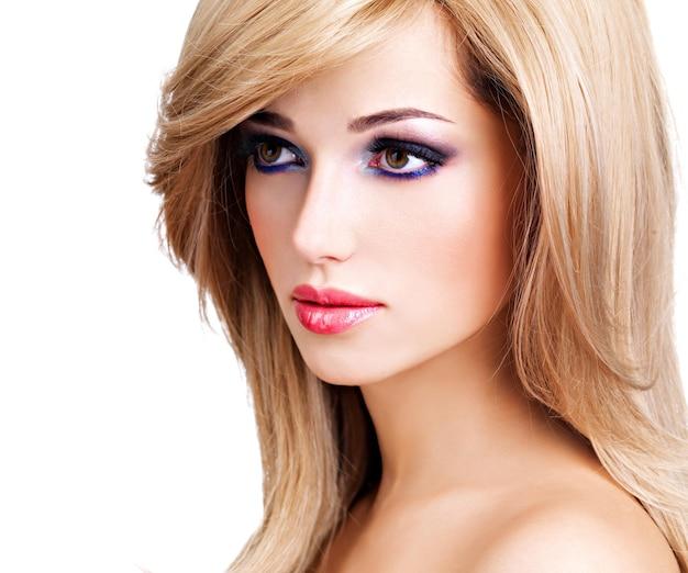 Close-upportret van een mooie jonge vrouw met lange witte haren. mannequin poseren over witte muur