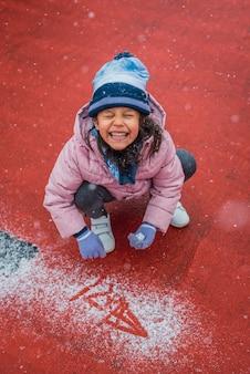 Close-upportret van een opgewonden meisje dat met verse sneeuw speelt tijdens een sneeuwval in de winter