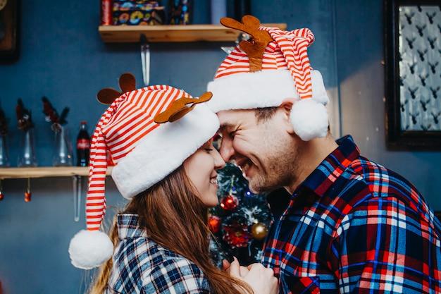 Close-upportret van een paar in liefde in nieuwjaarhoeden.