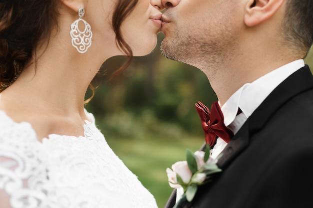 Close-upportret van een schitterende bruid en modieuze bruidegom die tijdens de huwelijksceremonie kussen.