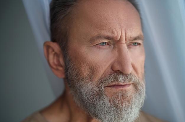 Close-upportret van een serieus nadenkend grijsharig bebaard, besnorde volwassen man die in de verte staart
