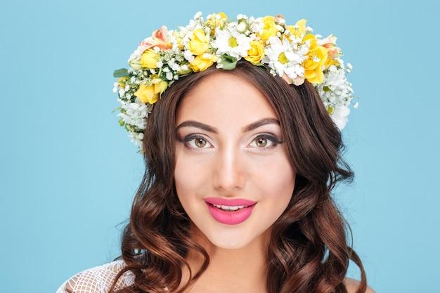 Close-upportret van een sexy brunette die bloemdiadeem draagt dat op de blauwe achtergrond wordt geïsoleerd