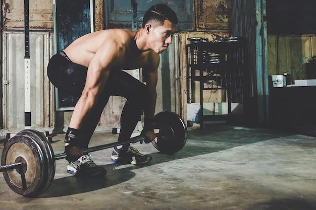 Close-upportret van een spiermensentraining met barbell bij lokale gymnastiek