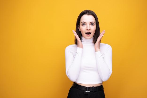 Close-upportret van een verraste brunette op een gele achtergrond.
