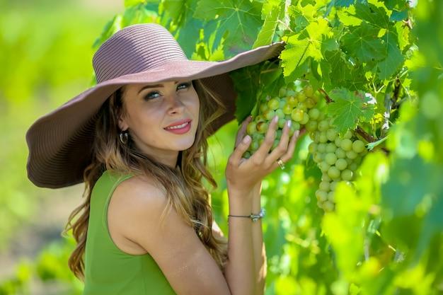 Close-upportret van een vrij jonge vrouw die een tros druiven in haar handen houdt