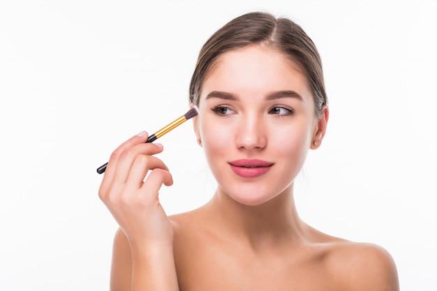 Close-upportret van een vrouw die droge kosmetische toon- stichting op het gezicht toepassen die make-upborstel gebruiken die op witte muur wordt geïsoleerd