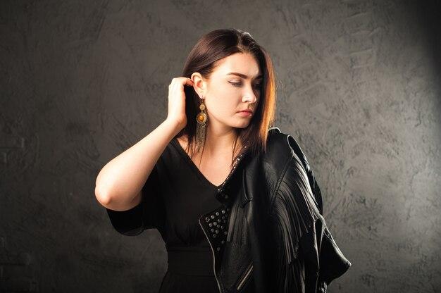 Close-upportret van een vrouw op een zwarte achtergrond. meisje in een zwart lederen jas en kopie ruimte.