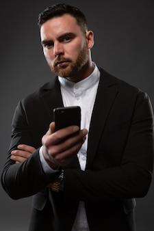 Close-upportret van een zakenman die berichten op zijn mobiele telefoon controleert.