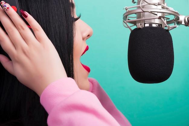 Close-upportret van een zingend meisje met rode lippen en microfoon op azuurblauwe muur