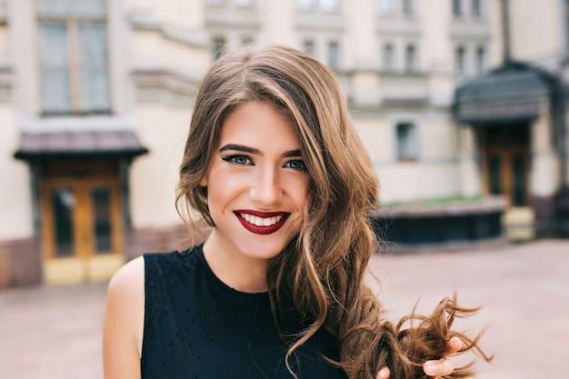 Close-upportret van efficiënt meisje met lang krullend haar glimlachen