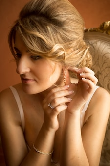 Close-upportret van elegante blondebruid die voor huwelijksdag voorbereidingen treft