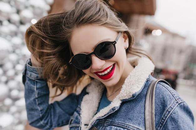 Close-upportret van emotioneel wit meisje in zonnebril die met haar donker haar spelen. buiten schot van glamoureuze vrouw in denim jasje stad rondlopen in lentemorgen.