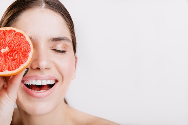 Close-upportret van energiek lachend meisje zonder make-up die haar gezicht behandelen met siciliaanse sinaasappel.