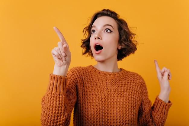 Close-upportret van enthousiast meisje dat met verraste gezichtsuitdrukking rondkijkt