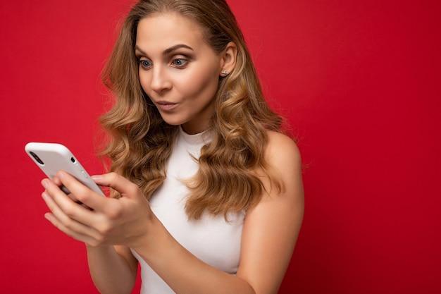 Close-upportret van ernstige geconcentreerde mooie jonge blondevrouw die wit t-shirt dragen dat over rode achtergrond wordt geïsoleerd die smartphone en sms-bericht via mobiele telefoon gebruiken die het gadjetscherm bekijken.