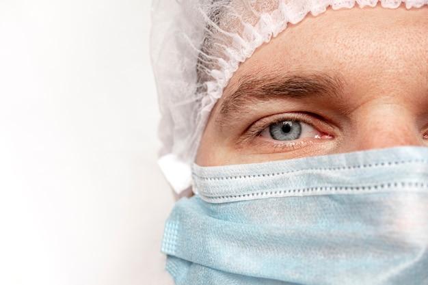 Close-upportret van ervaren chirurg, arts met masker, klaar om in het ziekenhuis te werken. de ogen van de dokter. covid-19. pandemie. de man is veilig en trots op zichzelf. geneeskunde, ziekenhuis en artsen concept