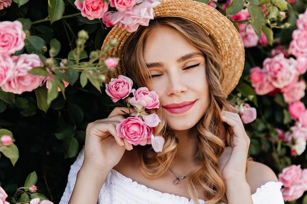 Close-upportret van extatisch krullend meisje poseren met rozen. buiten schot van aantrekkelijke vrouw in strooien hoed genieten van zomerdag.