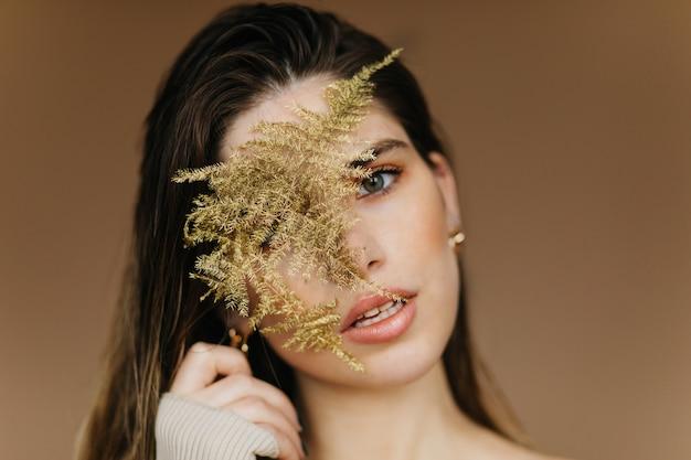 Close-upportret van fascinerend wit meisje met plant. geïnspireerde kalme vrouw die zich op bruine muur bevindt.