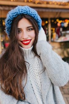 Close-upportret van fascinerende donkerharige dame met groene ogen die op kerstmis wachten en lachen. foto van betoverend meisje met lang kapsel draagt blauwe gebreide muts en witte wanten.