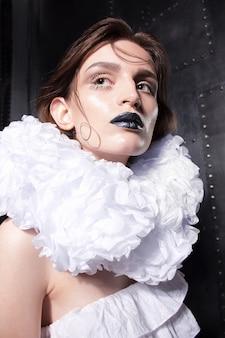 Close-upportret van flamboyante mooie vrouw met natte huidsamenstelling en kapsel in wit gekleed voor halloween- of kostuumpartij.