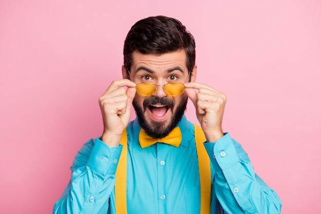 Close-upportret van funky blije kerel gele bril aan te raken