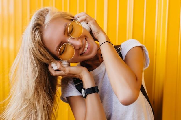Close-upportret van gebruinde charmante vrouw het luisteren muziek met gesloten ogen op geel