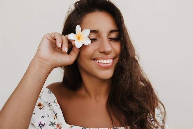 Close-upportret van gebruinde dame met sneeuwwitte glimlach poseren met bloem op witte muur
