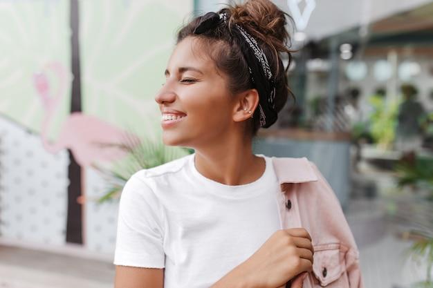 Close-upportret van gebruinde donkerharige vrouw met stijlvol broodje, glimlachend tegen muur van bar met geschilderde flamingo's