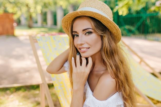 Close-upportret van geïnspireerd meisje met licht gebruinde huid die met haar lang glanzend haar speelt. buiten foto van lachende jonge vrouw in vintage schipper en witte zomerjurk.