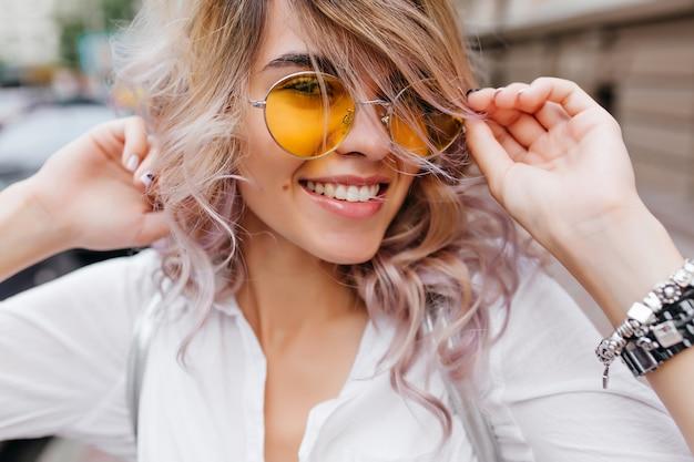 Close-upportret van geïnspireerde jonge vrouw die en haar blonde haar lacht raakt