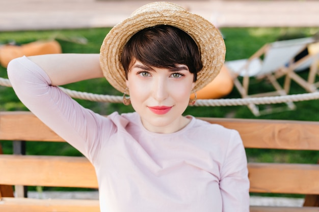 Close-upportret van geïnspireerde jonge vrouw met groene ogen, zittend op een houten bankje met gras