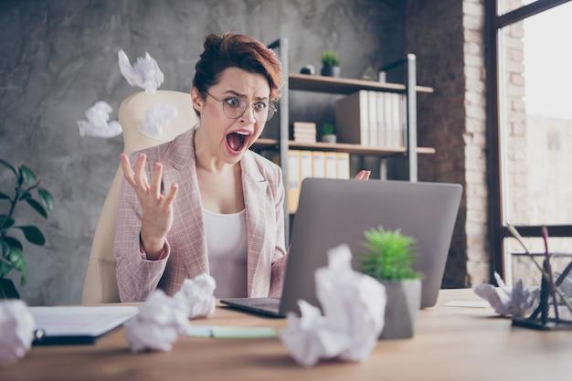 Close-upportret van gekke verontwaardigde dame die documenten schreeuwt