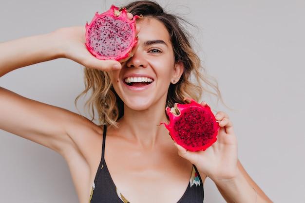 Close-upportret van gelooid meisje met lichte ogen die drakenfruit dichtbij gezicht houden. binnen schot van schattige krullende vrouw poseren met smakelijke rode pitaya.